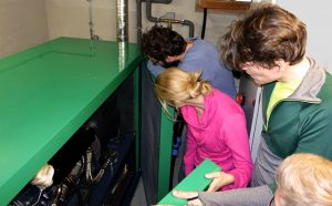 Studierenden schauen sich das Blockheizkraftwerk an (Foto: Stephan Baur)