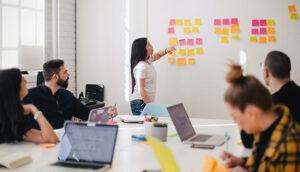 Ein Team aus Studierenden arbeitet mit Laptops und Post-Its
